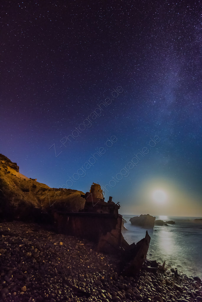 Milky way over ship wreck at the beach in Vila Nova de Milfontes, Portugal